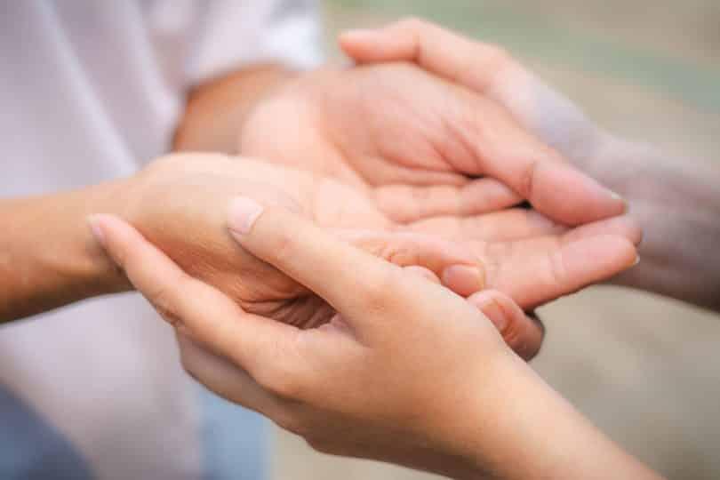 As mãos de duas pessoas. Todas com as palmas viradas para cima, enquanto uma das pessoas segura as mãos da outra por baixo.