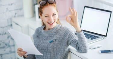 Mulher trabalhando em mesa de Home Office com notebook e celular enquanto segura papeis de escritório e sorri.