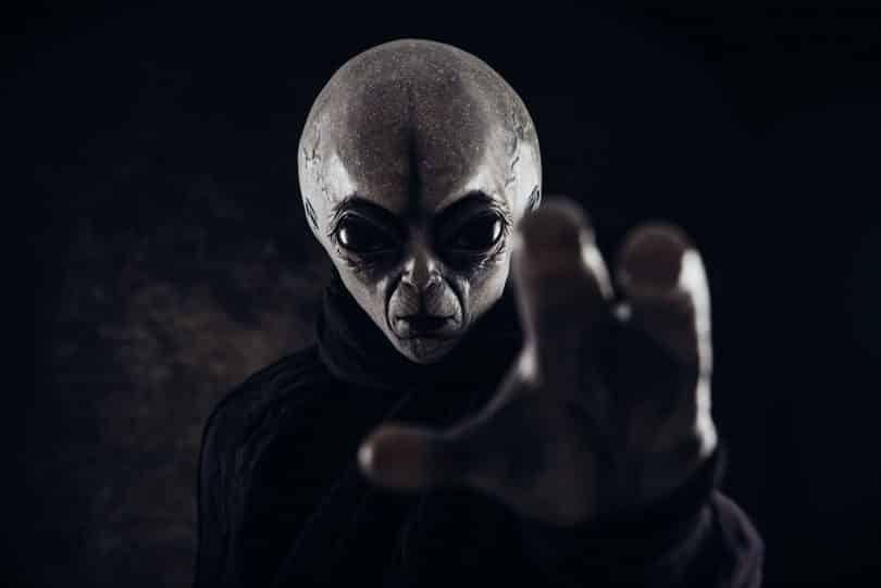 Figura humanoide com a mão estendida.