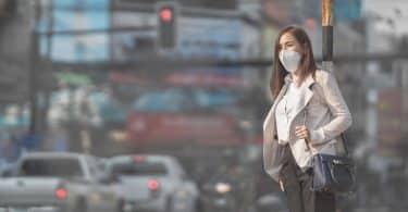 Mulher andando na rua com máscara de proteção no rosto