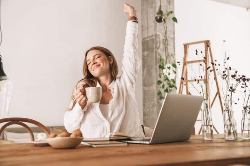 Mulher se espreguiçando com caneca na mão em trabalho em casa