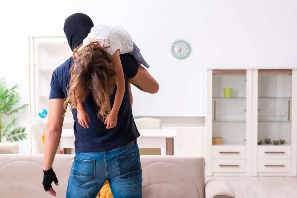 Homem com o rosto coberto por um gorro, segurando uma menina pelas pernas, jogada em seu ombro.