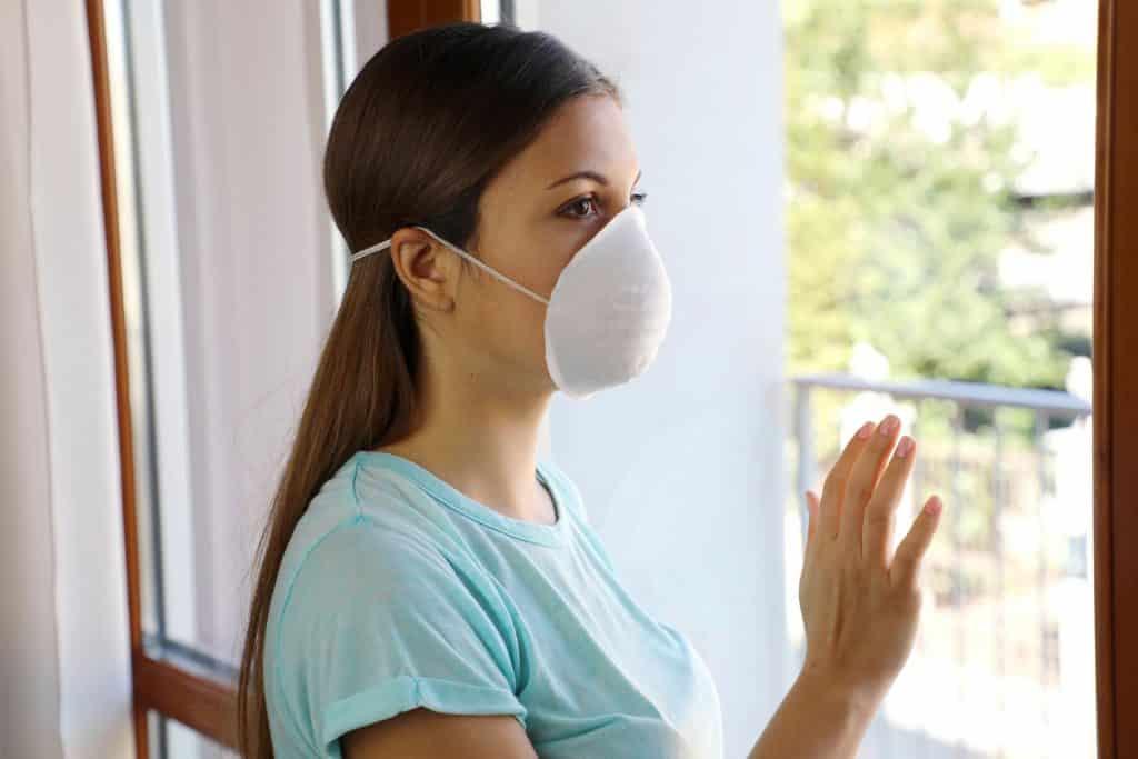Mulher ao lado de uma janela olhando para o lado de fora usando uma máscara de proteção