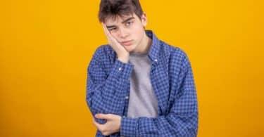 Rapaz com rosto apoiado na mão e expressão de desânimo
