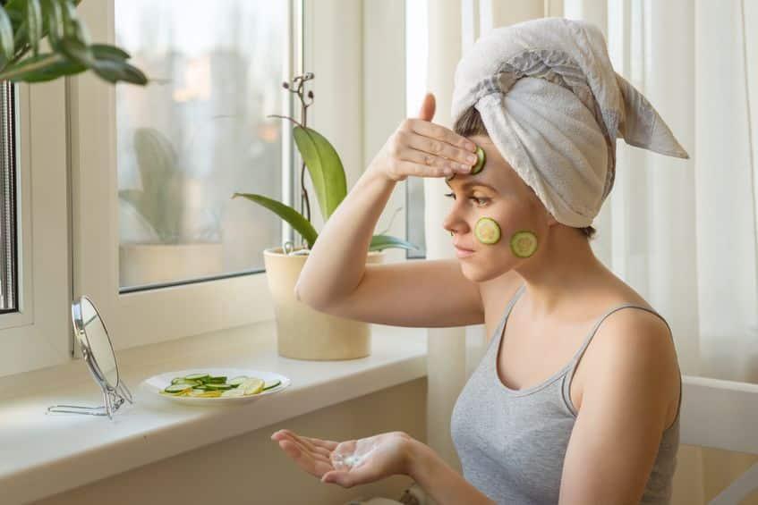 Mulher com pepinos no rosto olhando no espelho
