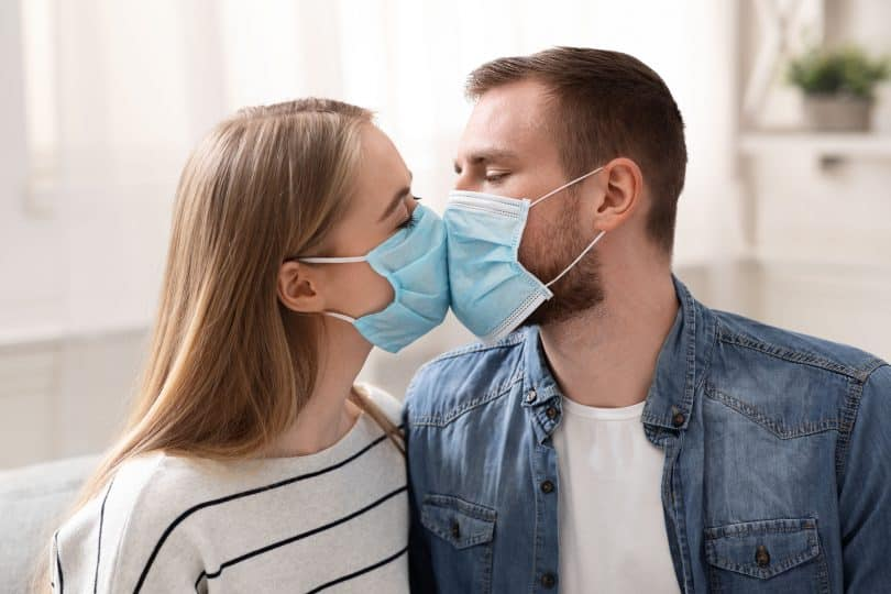 Casal em quarentena, beijando-se com máscaras faciais de proteção.