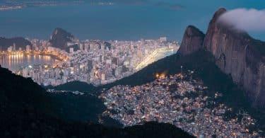 Vista aérea do Rio de Janeiro, do lado direito, uma favela acesa em topo de morro, enquanto na parte de baixo, perto do mar, prédios grandes de classe alta.