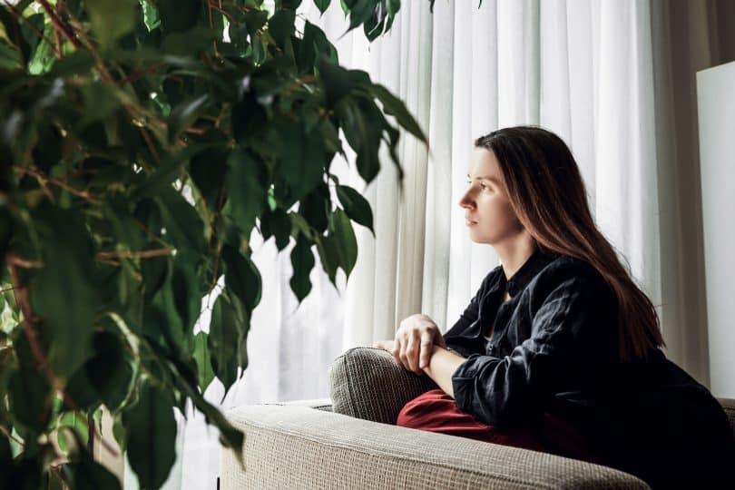 Mulher sentada em sofá, sozinha, olhando para uma janela.