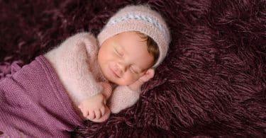 Bebê recém-nascido, enrolado em cobertores, esboçando um sorriso.