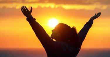 Mulher de costas com braços abertos para o alto e sol ao fundo