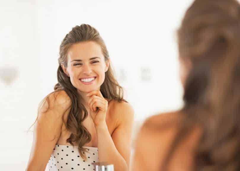 Mulher sorrindo enquanto olha seu reflexo no espelho