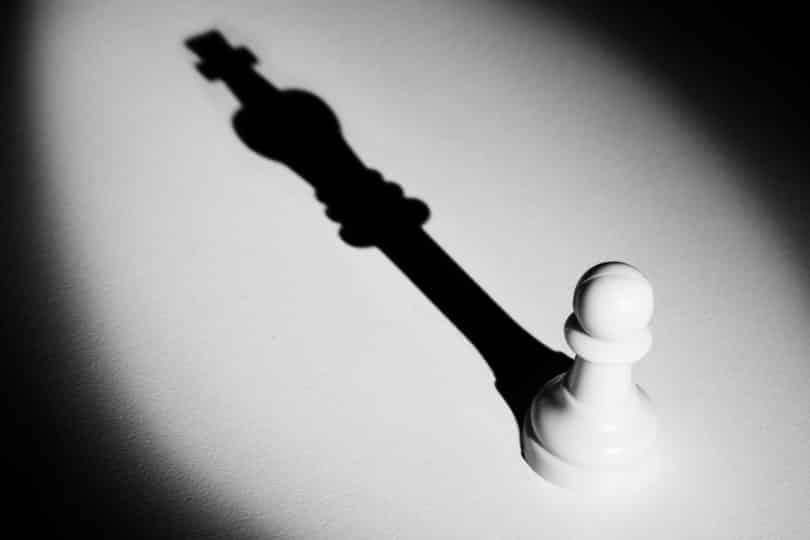 Um peão de xadrez recebendo luz, e sua sombra mostra um rei do xadrez.