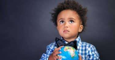 Menino segurando mini globo terrestre com roupa social olhando para cima