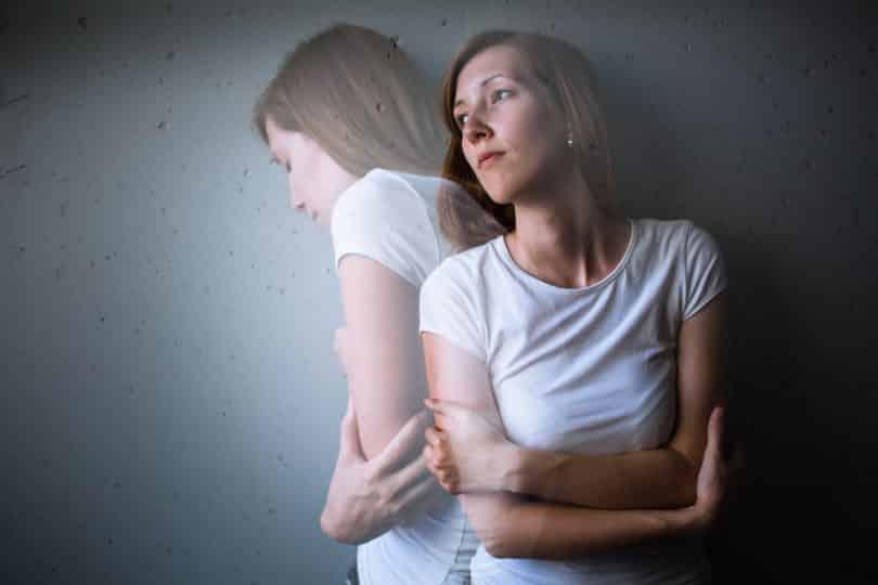 Mulher encostada na parede com braços cruzados e outra imagem saindo para o outro lado