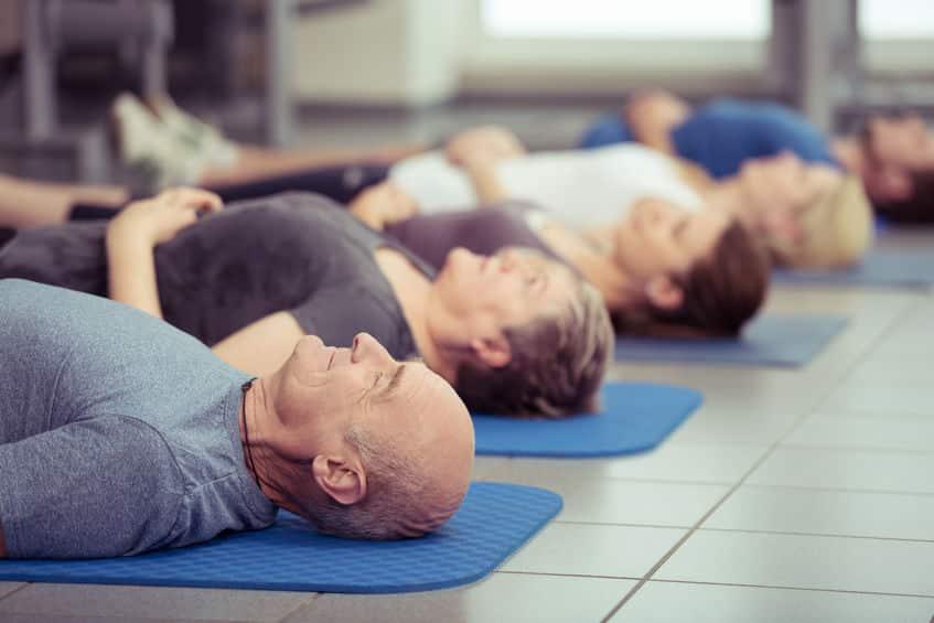 Pessoas deitadas meditando