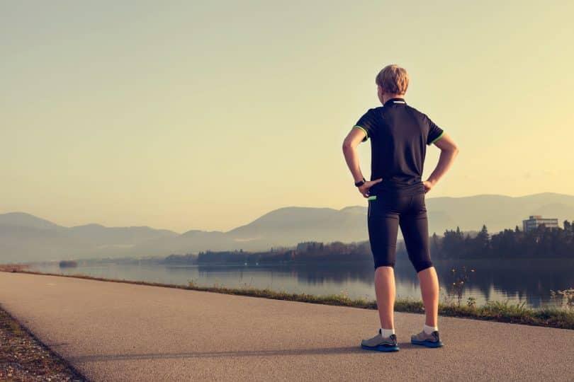 Homem com roupas de corrida parado em pé, de costas, no meio de uma estrada.