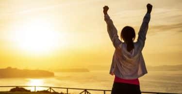 Silhueta de uma mulher de costas, com as mãos para o alto, ao pôr do sol.