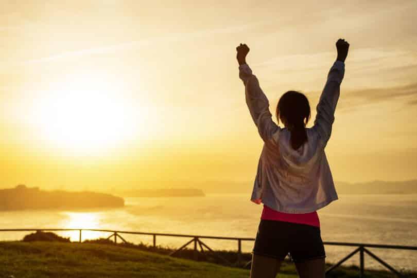 Mulher em frente ao mar e ao pôr do sol com os braços levantados