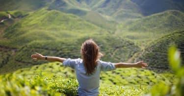 Mulher de costas sentada em montanha com área verde ao fundo e braços abertos