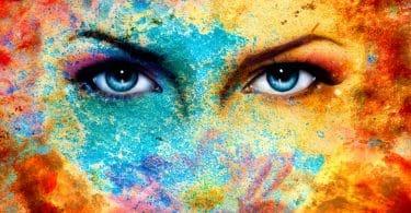Par de olhos azuis humanos, mesclados em um fundo com pontos de cores diferentes espalhadas.