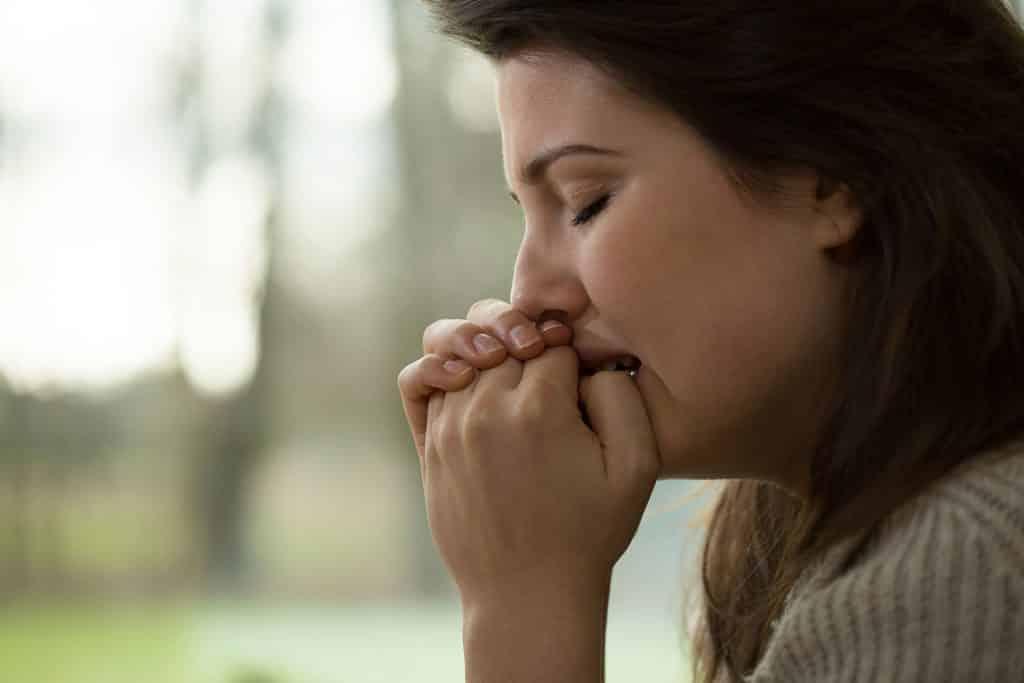 Mulher triste com as suas mãos juntas encostadas na boca