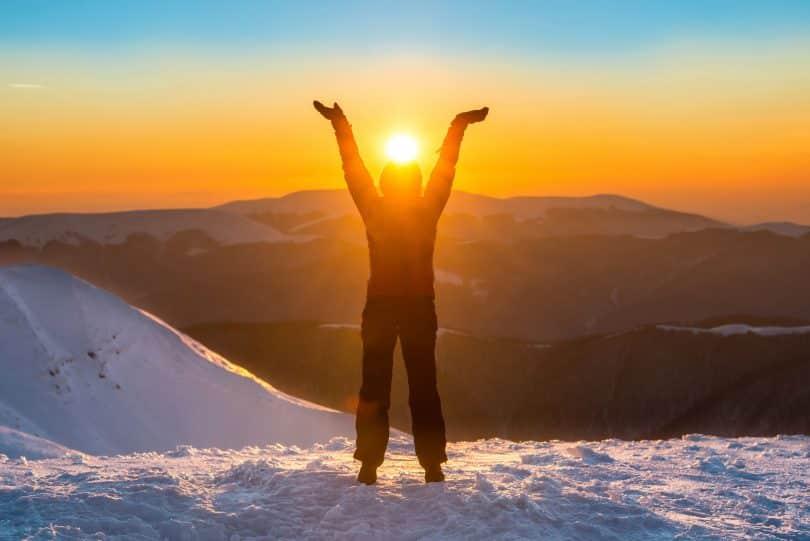 Pessoa com os braços erguidos em meio a neve. Ela está no pico de uma montanha.