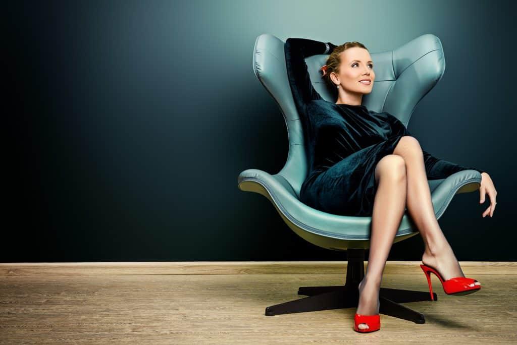 Imagem de uma mulher sensual vestindo um vestido preto de veludo e calçando um sapato de salto alto vermelho. Ela está sentada em uma poltrona de couro cinza.