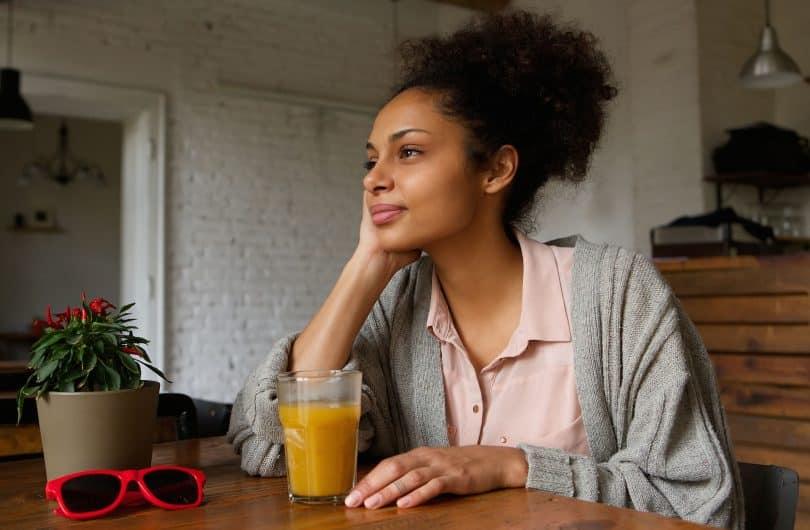 Mulher sentada na mesa da cozinha segurando um suco e olhando para frente pensativa