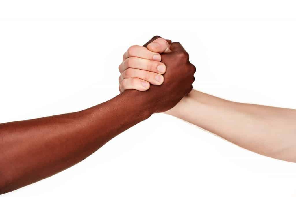 Imagem de dois braços - um negro e outro branco. Eles estão se cumprimentando.