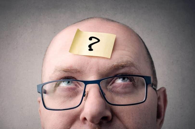 Homem com post it na testa com ponto de interrogação