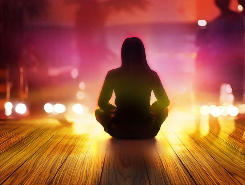 Mulher meditando com velas ao redor