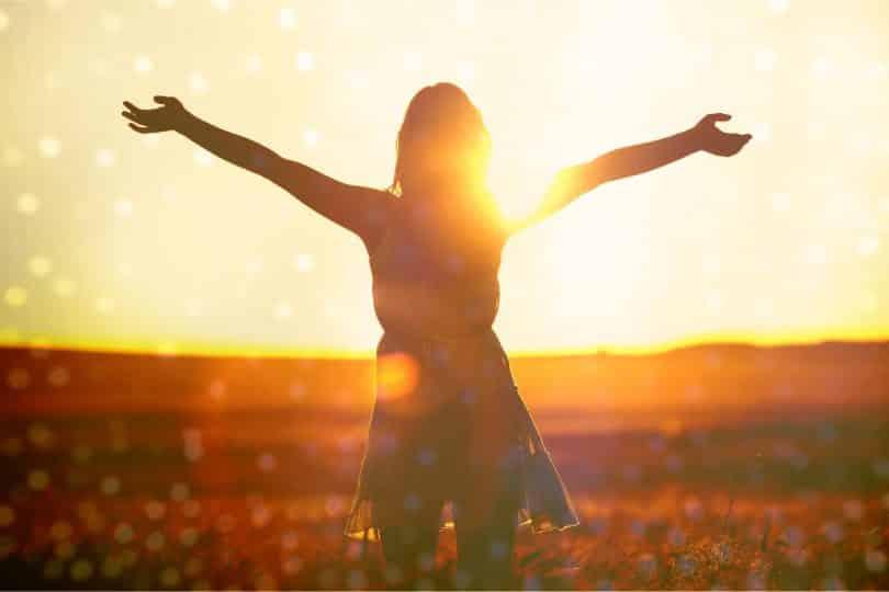 Mulher de costas em um campo, de braços abertos, ao pôr do sol.