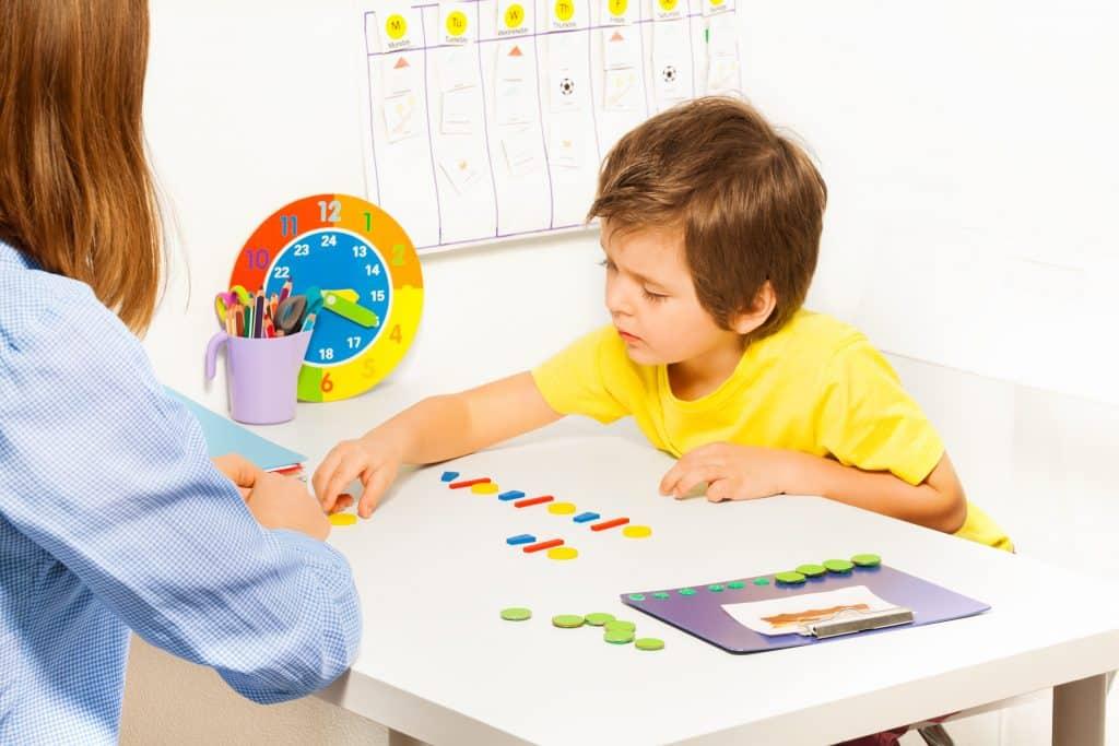 Imagem de uma criança jogando e montando um quebra-cabeça. Ela está sendada de frente com uma mulher que está observando-a. A mesa é branca e sobre ela tem os jogos infantis e um relógio de parede colorido.
