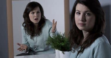 Mulher em frente a um espelho. Ela olha para a câmera com olhar cansado, enquanto seu reflexo, olha para ela mesma com expressão de choque.