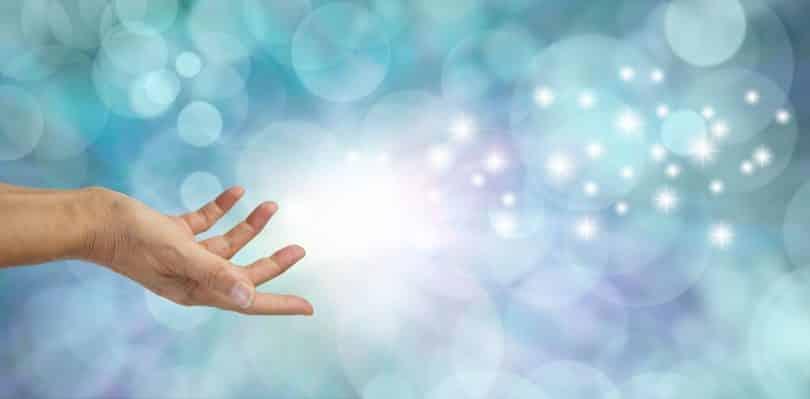 Mão estendida com ilustração de pontos de luz saindo dela, como uma força energética.