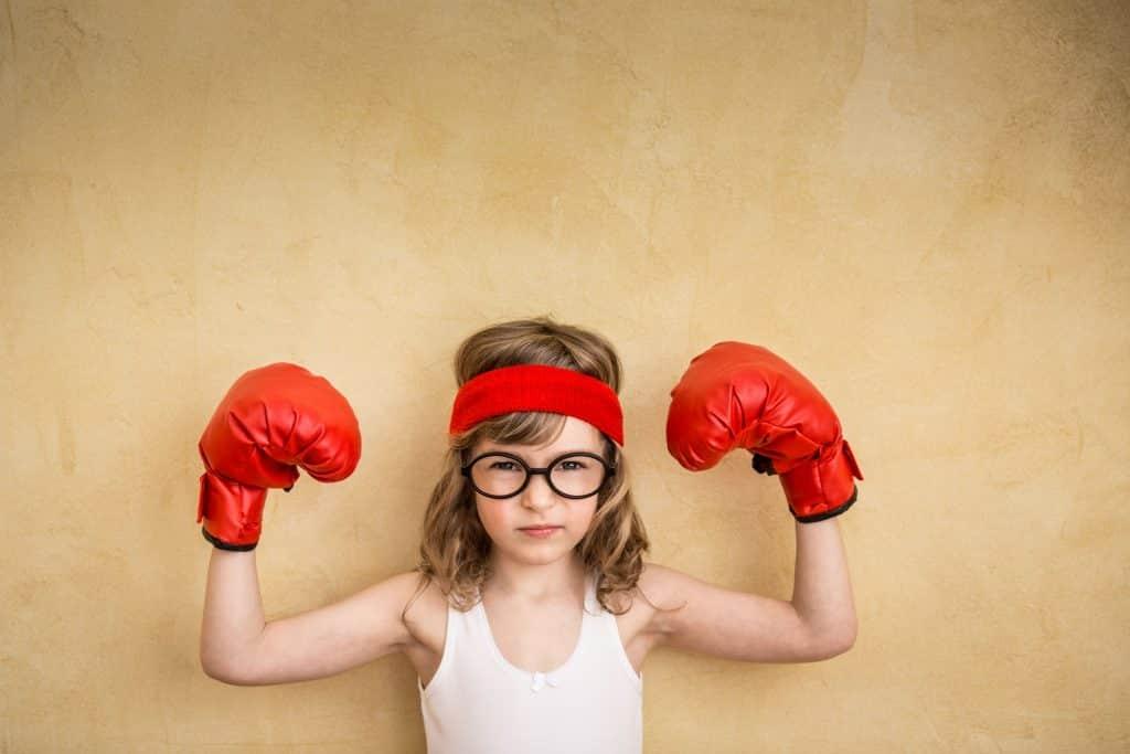 Menina pequena com luvas de boxe e óculos. Ela faz pose flexionando os braços para mostrar seus músculos - que não existem, já que ela é uma criança.