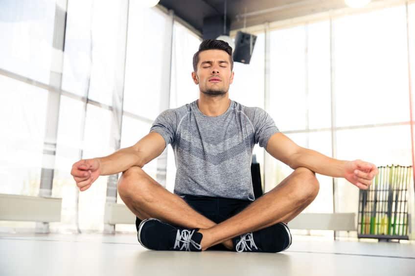 Homem meditando e caixa de som ao fundo