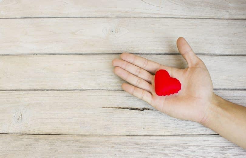 Mão estendida com um coração de pano na palma, oferecendo-o a alguém.