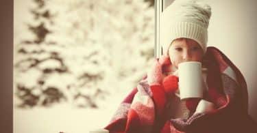 Menina enrolada em um cobertor tomando algo na xícara