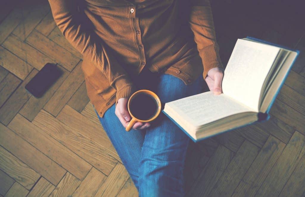 Mulher sentada no chão segurando um livro aberto com uma mão, e uma xícara de café com a outra mão.