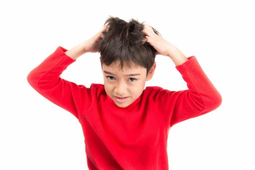 Imagem de uma criança vestindo uma blusa de frio vermelha, Ela está com as duas mãos coçando a cabeça.