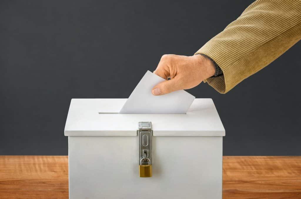 Pessoa colocando um papel dentro de uma urna lacrada com cadeado.