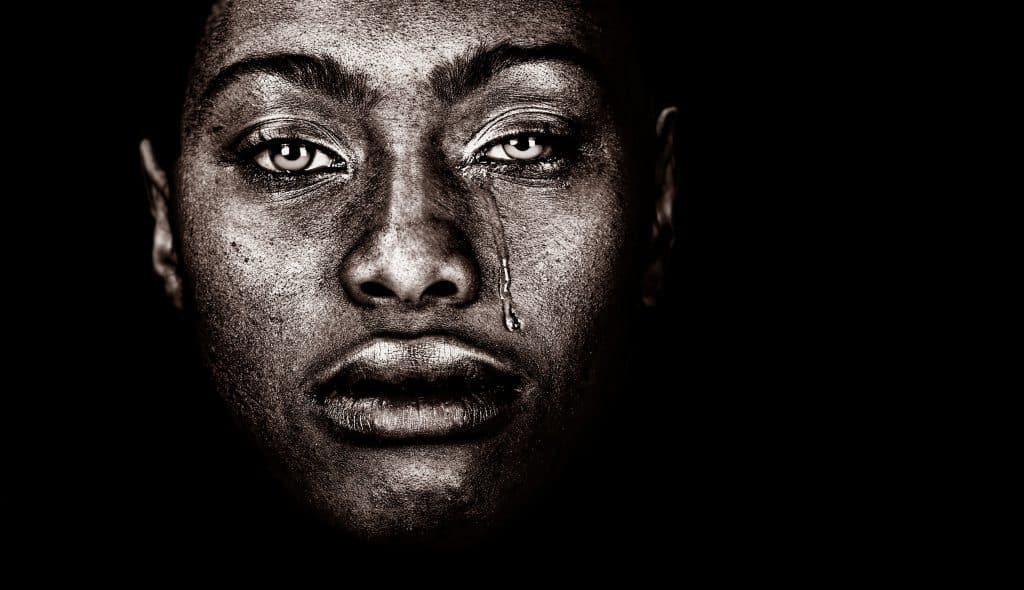 Imagem de um rosto negro. Uma lágrima desce de um dos olhos da pessoa.