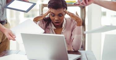 Mulher com os dedos nas têmporas, a boca aberta com expressão de surpresa em frente a um computador, e pessoas ao seu lado lhe oferecendo tablets e celulares.