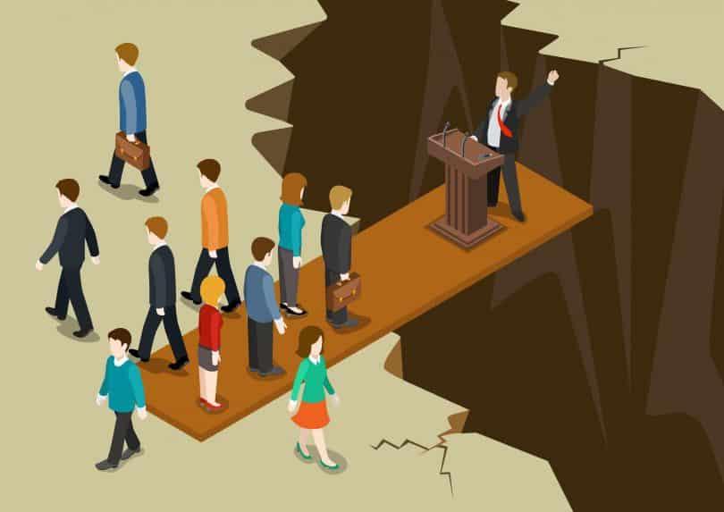 Desenho de tábua comprida entre chão e um abismo. Do lado da tábua que está no chão, estão várias pessoas de pé. Do outro lado da tábua, sobre o abismo, está um político falando em um palanque.