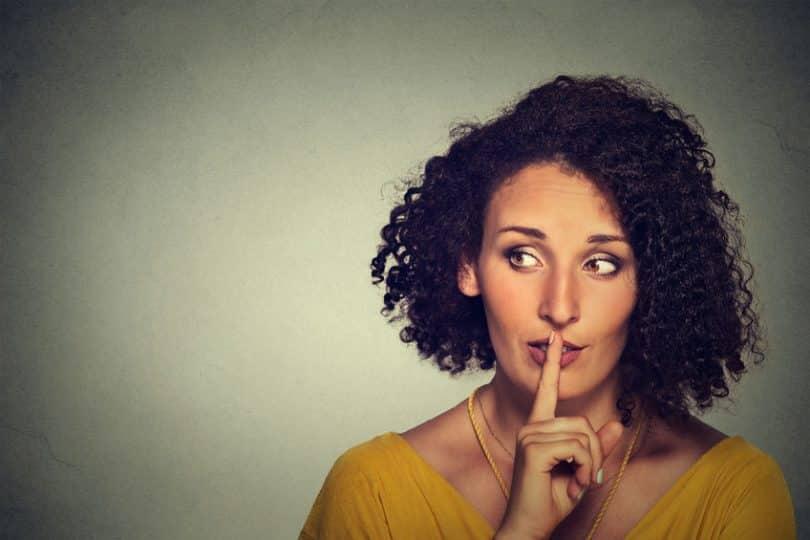 Mulher com dedo na boca em sinal de silêncio olhando para o lado