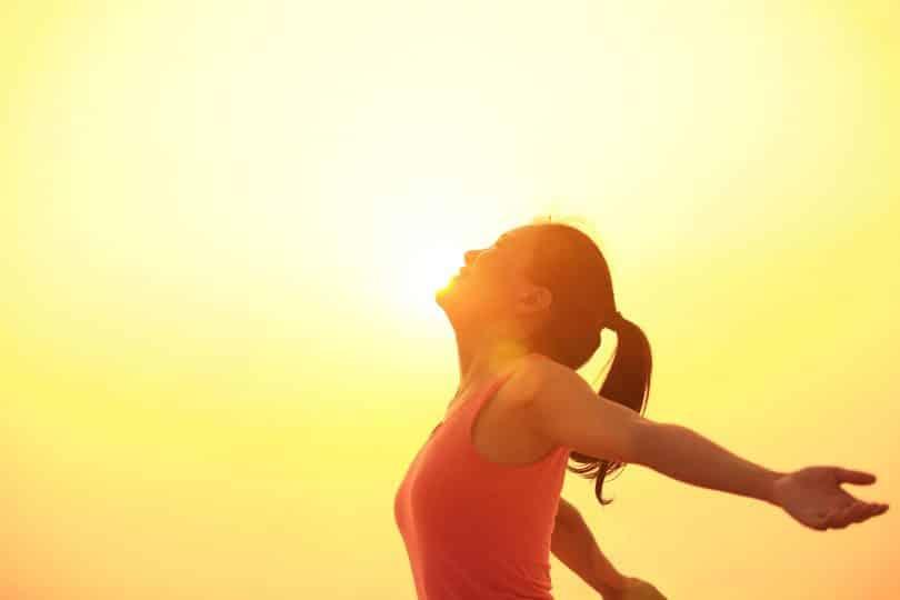 Mulher de braços abertos, sorrindo sob o pôr do sol.