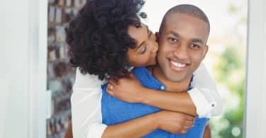 Homem segura mulher nas costas enquanto ela beija sua bochecha.