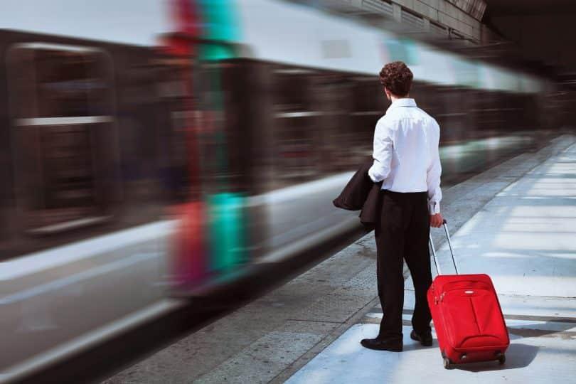 Homem em pé, parado, enquanto um trem passa em alta velocidade a sua frente.
