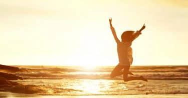 Mulher pula com os braços erguidos e abertos. Ela está em uma praia.